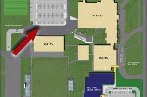 WORK TO BEGIN soon on a new parking lot on the Kingfi sher High School campus (indicated by red arrow, above) to replace existing parking that will be lost in the construction of the 7th & 8th Grade Center.